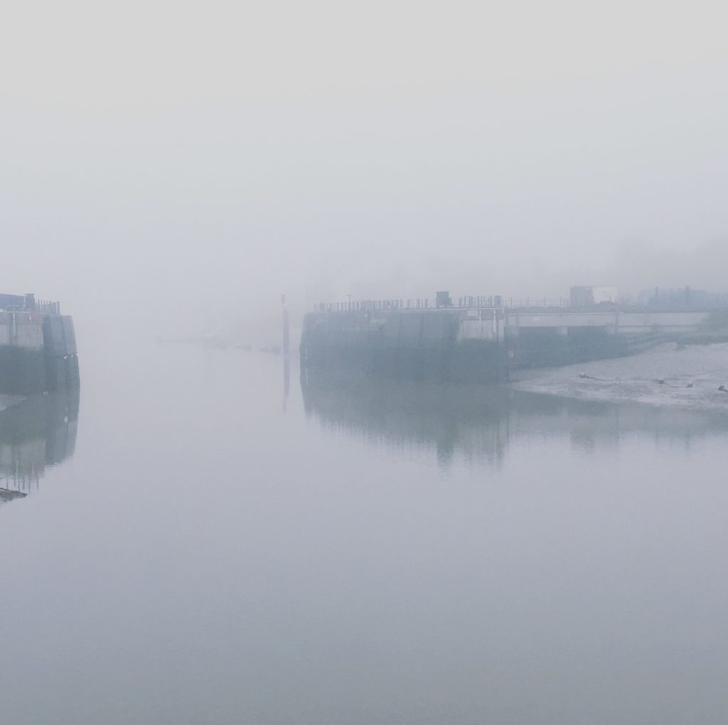 View of River Colne flood barrier in fog, Essex